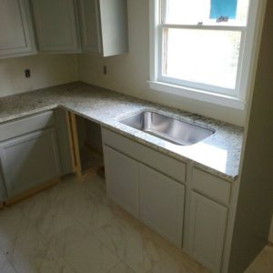 Moon Light granite kitchen countertops featuring an under mount single bowl stainless steel sink