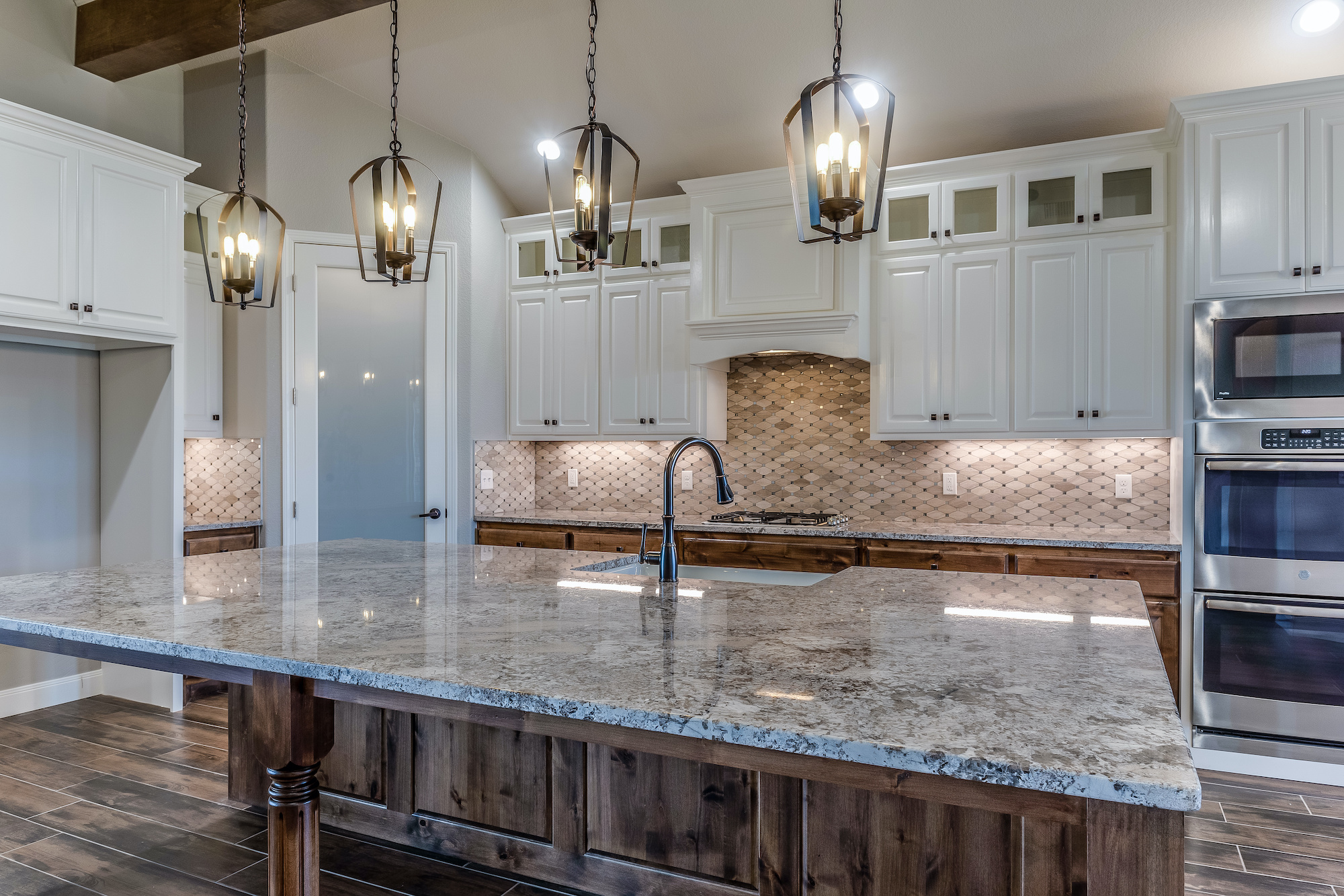 Kitchen with stone countertops, tile backsplash and custom cabinets