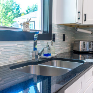 Absolute Black granite kitchen countertops stacked glass tile backsplash white cabinets stainless steel appliances